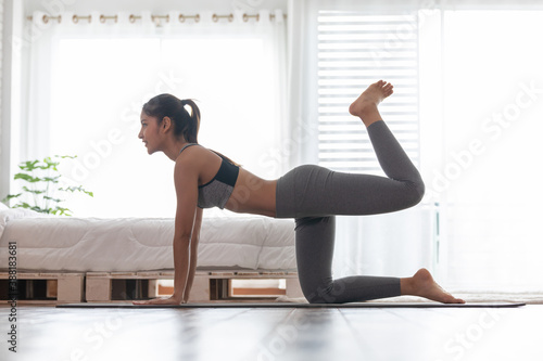 Obraz Athletic Healthy Asian indian woman in sportswear workout excercise at home in bedroom,Young woman with slim body cardio aerobic exercises healthy lifestyle concept - fototapety do salonu