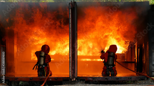 Fotomural Firefighter fighting with flame using fire hose chemical water foam spray engine