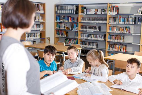 Obraz Group of school kids studying in school library with friendly female teacher.. - fototapety do salonu