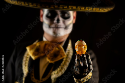 Mexican charro holding a candy skull in his hands on day of the dead Fototapet