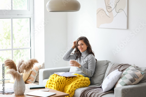 Fotografie, Obraz Beautiful young woman drinking tea while reading book at home