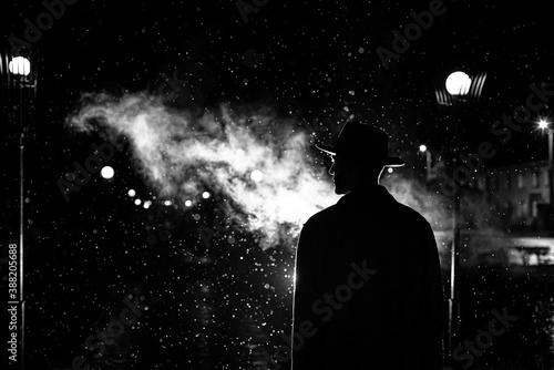 Fototapeta dark silhouette of a man in a hat in the rain on a night street in a city