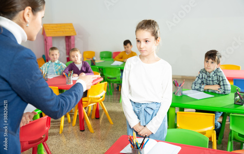 Obraz Portrait of upset schoolgirl standing at pupils desk, listening reprimanding of strict woman teacher - fototapety do salonu