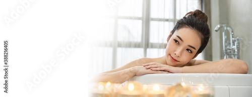 Closeup beautiful asian young  woman lying down soke in bath tub at Asian luxury spa and wellness center Fototapeta