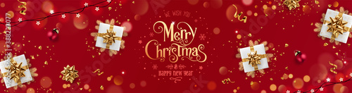 Obraz Gold Merry Christmas and New Year text on red holiday background with gift boxes, fir branches, ribbons, decoration, sparkles, confetti, bokeh, light. Xmas card. Vector Illustration, realistic vector - fototapety do salonu