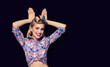 Leinwandbild Motiv Excited happy woman holding hands on head in rabbit ears gesture, over black color background
