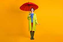 Full Length Photo Portrait Of Happy Woman Standing Under Umbrella Isolated On Vivid Yellow Colored Background
