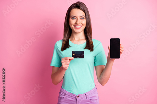 Obraz Photo portrait of woman holding phone with blank space credit card isolated on pastel pink colored background - fototapety do salonu