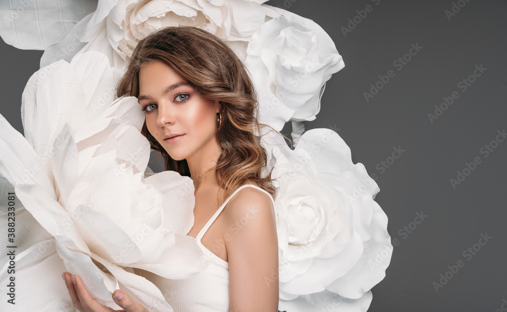 Fototapeta Portrait of beautiful young woman surrounded by flowers