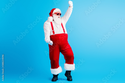 Full length photo of cool funky overweight santa claus dance x-mas christmas newyear party club wear sunglass suspenders overall isolated over blue color background