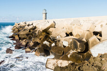 Wave Crashing Against Concrete Tetrapods Wave Breakers With A Small Lighthouse In The Background In The Lebanese Coastal Town Batroun, Lebanon