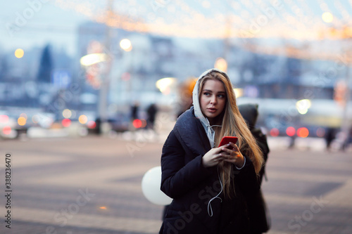 Slika na platnu Caucasian girl woman in a long down coat in the city with a phone, the concept o