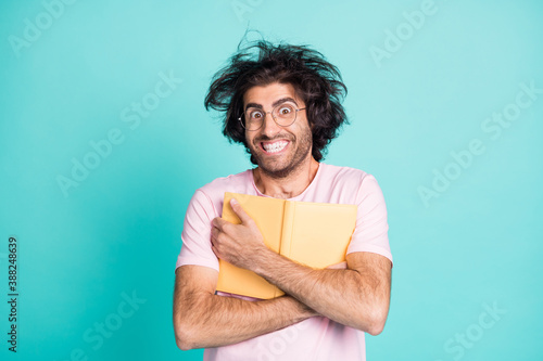Photo of weird hairstyle satisfied man arms hold cuddle book to chest toothy smile isolated on turquoise color background