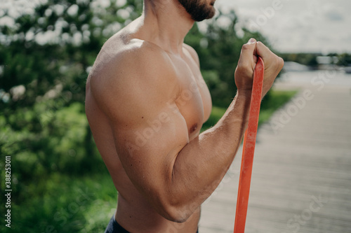 Cropped shot of unrecognizable muscular man has workout biceps exercise stands in profile shows strong muscles, uses resistance band, strives for strong body Fototapet