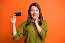 Photo Of Crazy Funky Young Lady Showing Credit Card Open Mouth Palm Cheek Wear Green Shirt Isolated Orange Color Background