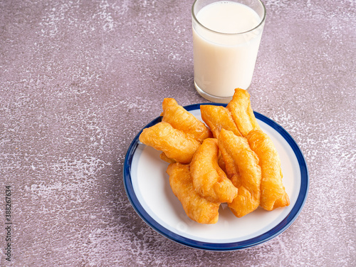 Cuadros en Lienzo Top view of deep-fried dough sticks or Chinese doughnut sticks on a white plate and a glass of soybean milk on gray stone background