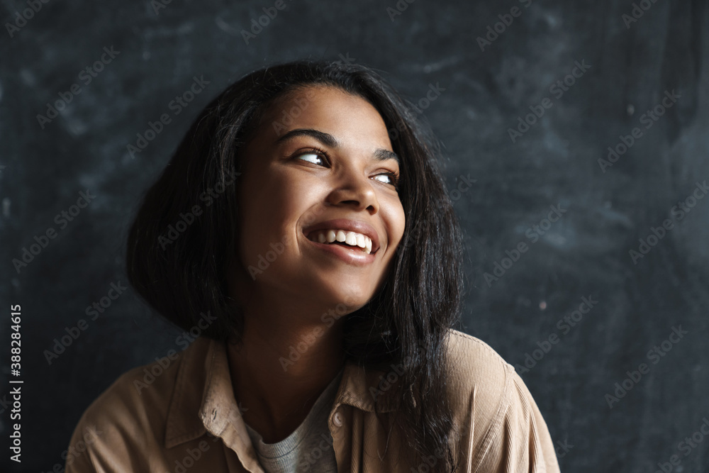 Fototapeta Happy african american woman smiling and looking aside