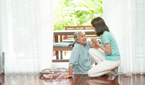 Fotografija Asian senior woman falling down on lying floor at home after Stumbled at the doorstep and Crying in pain and the nurse came to help support