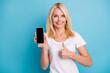 Leinwandbild Motiv Positive old lady hold smartphone select thumb up sign wear white t-shirt isolated blue color background