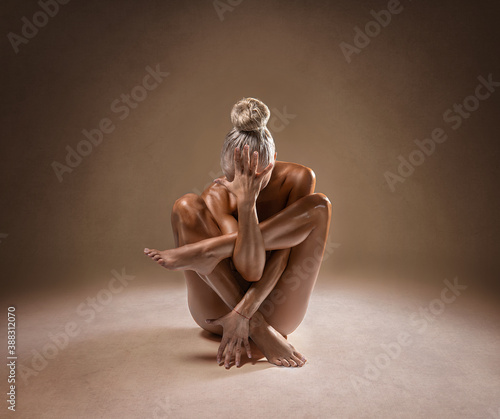 Beautiful nude sexy fitness girl with great figure flexing her perfect body in a yoga pose