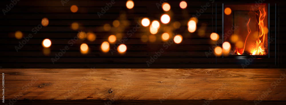 Fototapeta Illuminated rustic wooden table in front of an log fire with golden bokeh lights. Background for cozy evenings and space for your text and decorations.