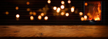 Illuminated Rustic Wooden Table In Front Of An Log Fire With Golden Bokeh Lights. Background For Cozy Evenings And Space For Your Text And Decorations.