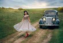 Young Beautiful Happy Retro Woman Near The Old Car. Attractive Elegant Lady In Vintage White Polka Black Dot Retro Dress. Pin-up Hairstyle. Cheerful Girl Standing On Road. Autumn Nature, Yellow Trees