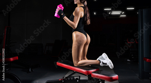 Obraz Tall athletic woman posing in the gym with a shaker. Fitness and bodybuilding concept. - fototapety do salonu