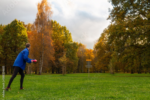 Obraz Young caucasian man in blue jacket playing disc golf on autumn play course with basket - fototapety do salonu