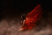 Young Beautiful Angel Woman With Red Wings Sits On A Cloud. Night Dark Sky Background With Stars And Space. Sexy Latex Dress. Valentine's Day Concept. Goddess Girl Watching The Universe From Cosmos