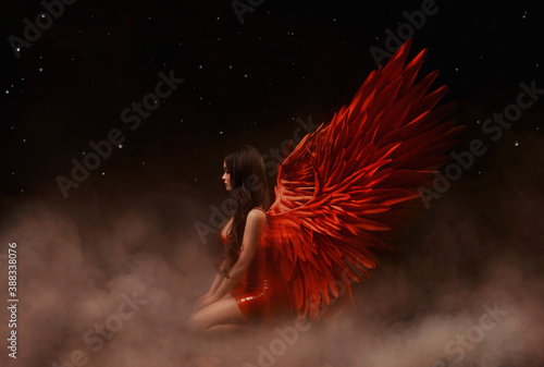 Young beautiful angel woman with red wings sits on a cloud Fototapet