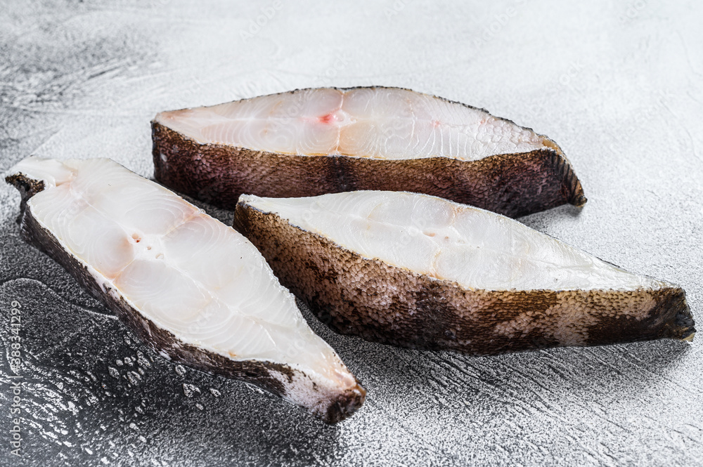 Fototapeta Raw fresh steak fish halibut on the stone table. White background. Top view