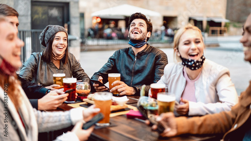 Fotografia Young friends drinking beer wearing face mask - New normal lifestyle concept wit