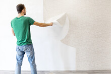 Young Man Tearing Old Wallpaper Off The Wall With Copy Space