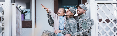 Happy military mother and father sitting near daughter pointing with finger, on Wallpaper Mural