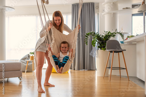 Obraz Happy young mother is swinging her cute little boy indoors and spending time together at home - fototapety do salonu