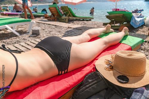 Obraz Woman wearing bikini laying on deck chair take sunbathing at the public sea beach - fototapety do salonu