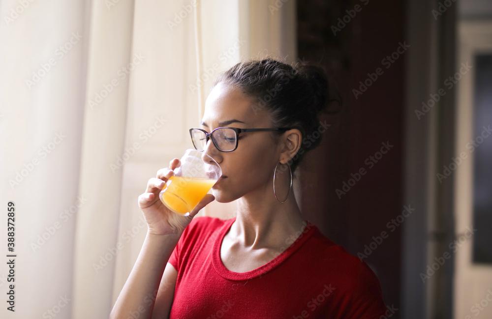 Fototapeta young woman drinks a orange juice