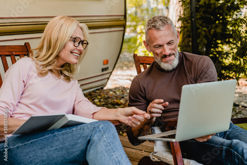 Mature handsome grey-haired man showing his blonde wife something amusing on his Wallpaper Mural