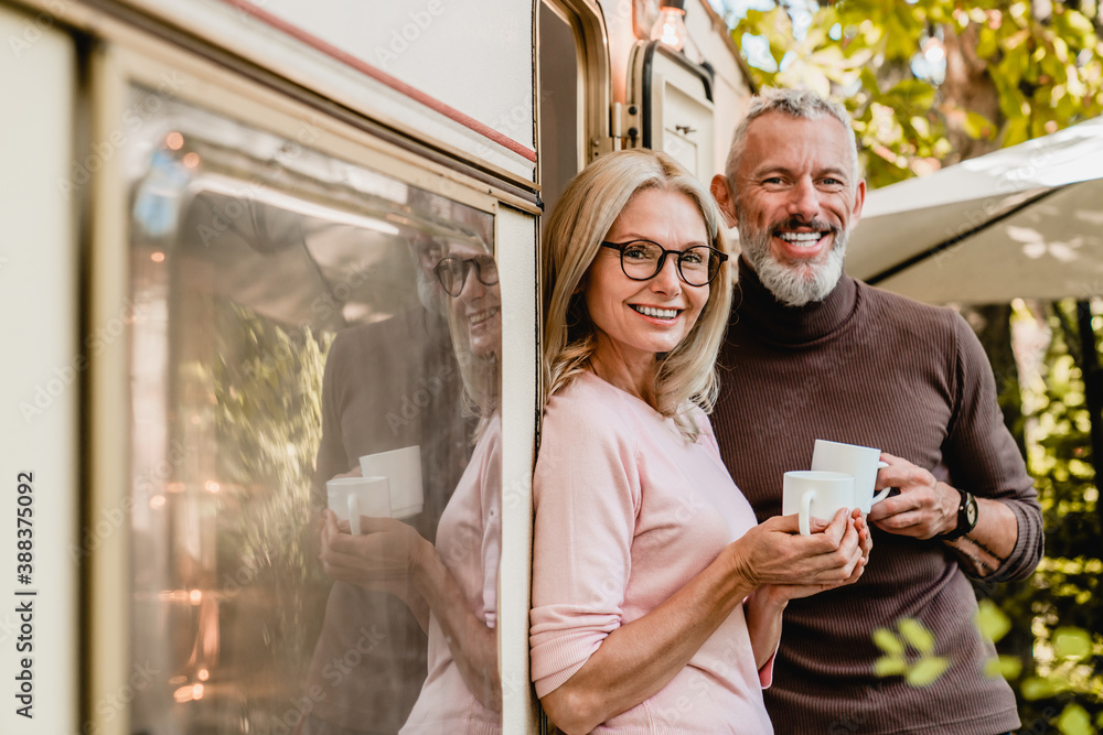 Fototapeta Portrait of happy successful mature couple smiling at the camera holding cups of coffee near their van