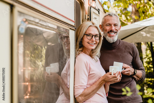 Obraz Portrait of happy successful mature couple smiling at the camera holding cups of coffee near their van - fototapety do salonu