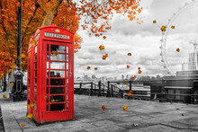 Concept Of London During Autumn Time With A Classic, Red Telephone Booth And Golden Colored Leafs Falling From The Trees