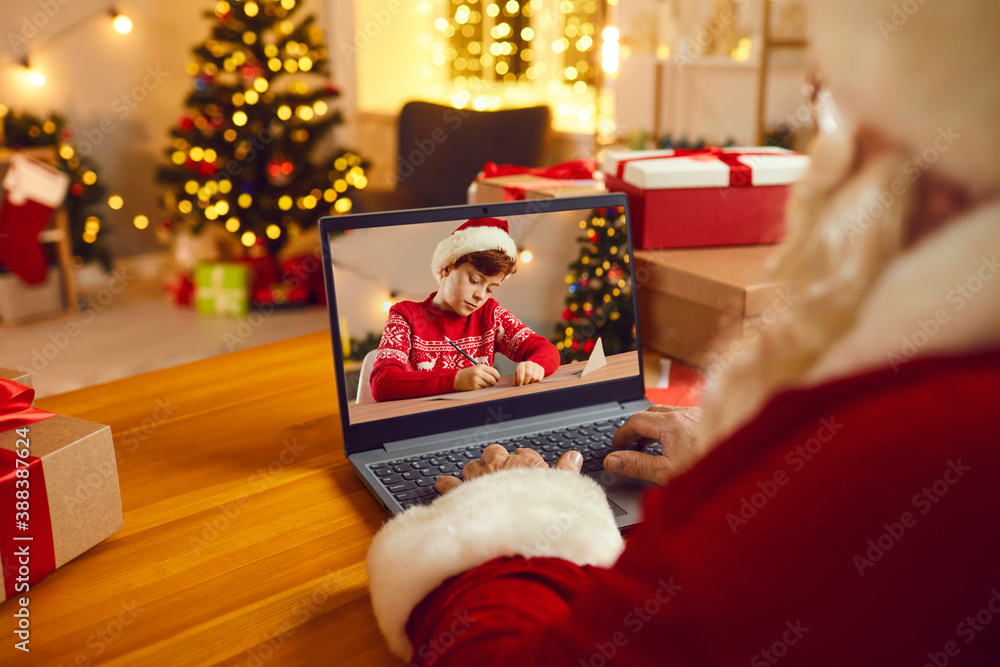 Fototapeta Santa Claus video calling little boy or using spying magic to see if kids are naughty or nice