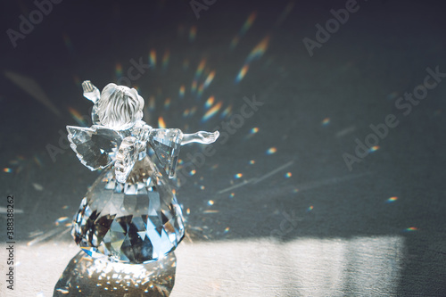 Leinwand Poster Crystal glass angel in the rays of the sun with reflecting, embossed sparkle