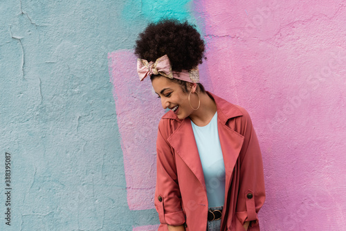 Young mixed woman with afro hairstyle smiling in a colorful background Fototapet