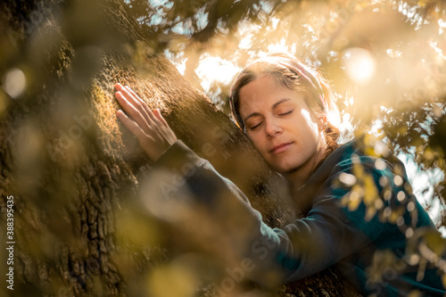 Close portrait of woman hugging the trunk of an old oak tree