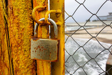 Close Up Yellow Color Paint Rusty Metal Closed Gate With Lock And Mesh On Seaside No Access To The Beach Concept