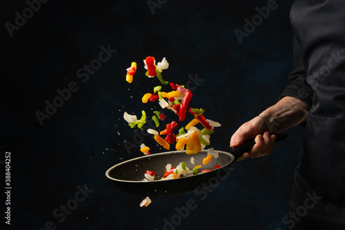 Fényképezés Close-up view of chef's hand throws up frying mix of colored vegetables above the pan on dark blue background