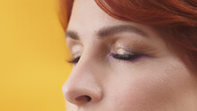 Close Up Of Closed Eyes With Purple And Gold Eyeshadow Of Mature Red Hair Woman. High Quality Photo