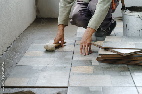 Fototapeta Close up on hands of unknown senior man craftsman using hammer to adjust and lay ceramic tiles on the balcony or terrace over adhesive cement in day - construction industry concept copy space obraz na płótnie